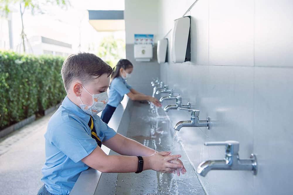 Os estudantes lavam as mãos e seguem os procedimentos de segurança